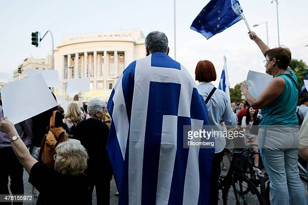 A protester wears a Greek national flag wrapped around his shoulders during a pro European Union demonstration in Thessaloniki Greece on Monday June...