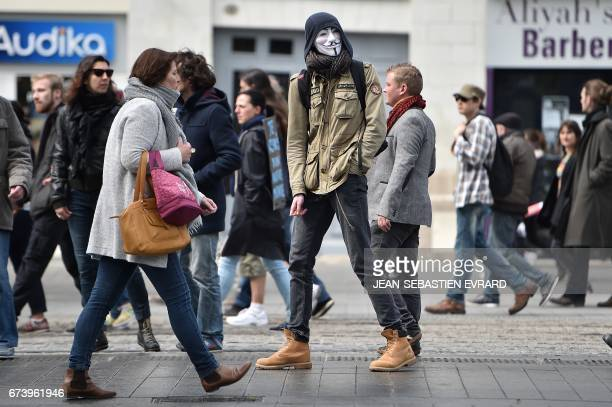 A protester wears a Guy Fawkes mask during a demonstration against the results of the first round of the French presidential election in Nantes...