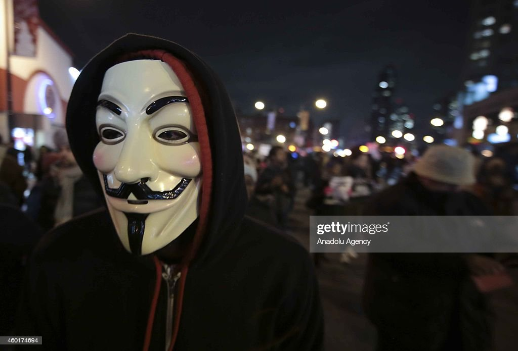 A protester wears a Guy Fawkes mask during a protest after a grand jury decided not to indict the police officer involved in the death of Eric Garner, in front of Barclays Center where the Brooklyn Nets - Cleveland Cavaliers NBA basketball game is played in New York, N.Y. on December 8, 2014.