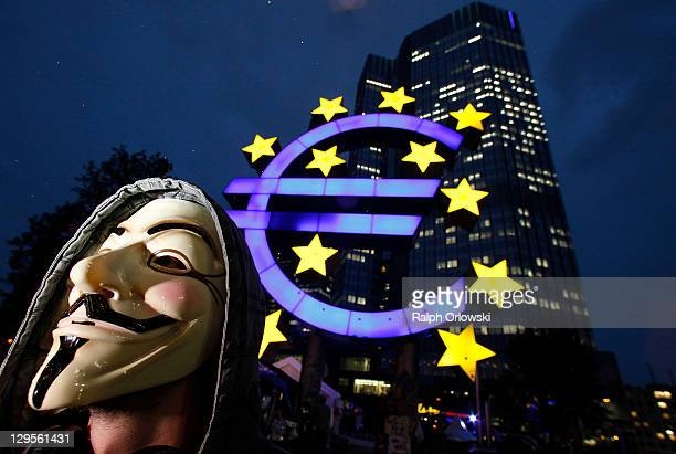A protester wears a Guy Fawkes masks while demonstrating inspired by the Occupy Wall Street protests in the United States in front of the...