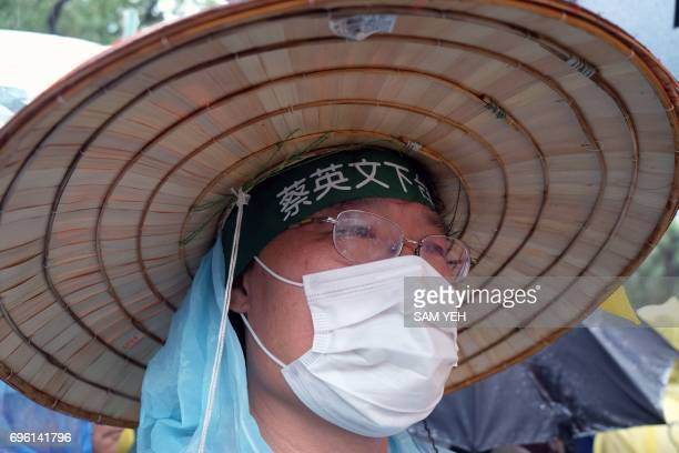 A protester wears a headband reading 'Tsai Ingwen step down' during a demonstration outside the Parliament in Taipei on June 15 2017 Hundreds of...