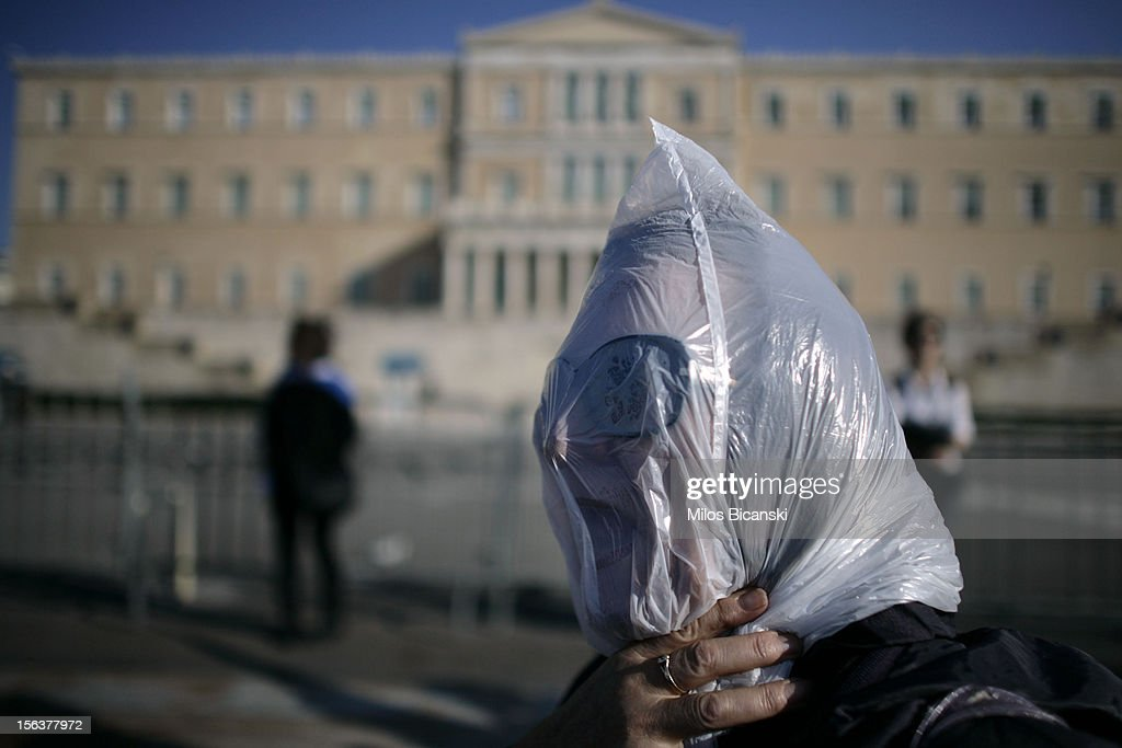 A protester wears a plastic bag on face during an anti-austerity protest on November 14, 2012 in Athens, Greece. Unions in Spain, Portugal and Greece went on strike in what has become the first broad-based anti-austerity action to protest government plans amid a wide economic scope across Europe.