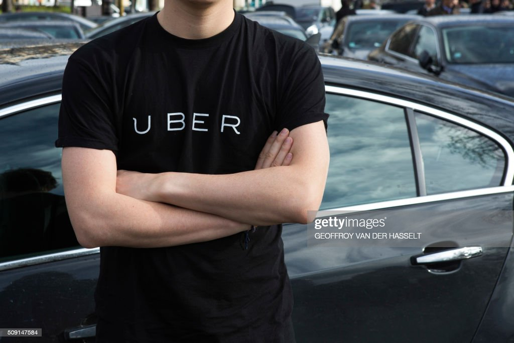A protester wears a shirt displaying the logo of smartphone ride service Uber during by a protest by non-licensed private hire drivers blocking the Place de la Nation in Paris on February 9, 2016. Members of services known in France as 'voitures de tourisme avec chauffeur' (VTC - Tourism vehicle with driver) have been protesting against assurances the French Prime minister has given to taxis. / AFP / Geoffroy Van der Hasselt