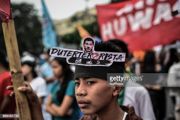 A protester wears an antiDuterte sign on a headband during Human Rights Day protests in Manila Philippines December 10 2017 On International Human...