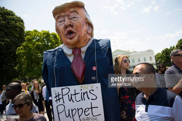 A protester wears an effigy of Donald Trump in front of the White House during a protest demanding an independent investigation in the Trump/Russia...