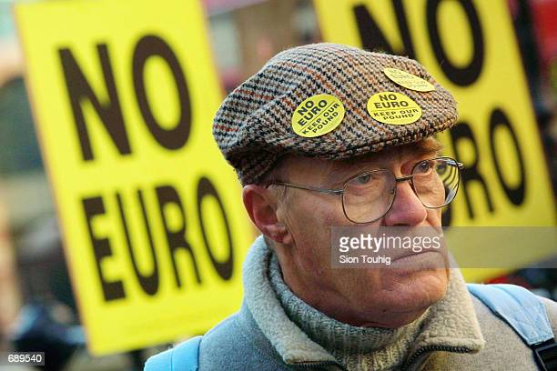 A protester wears antieuro stickers on his cap during a demonstration against the new currency January 2 2002 outside the Bank of England in London...