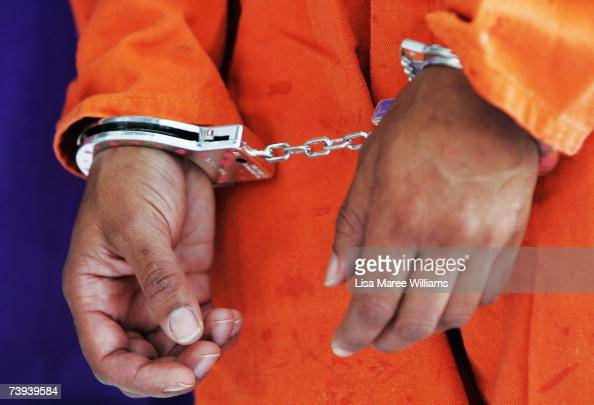 A protester wears handcuffs in support of Guantanomo Bay detainee and convicted terrorism supporter David Hicks April 21 2007 in Sydney Australia...