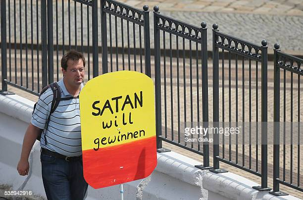 A protester who is holding a sign that reads 'Satan wants to win' walks outside the venue of the 2016 Bilderberg Group conference on June 9 2016 in...