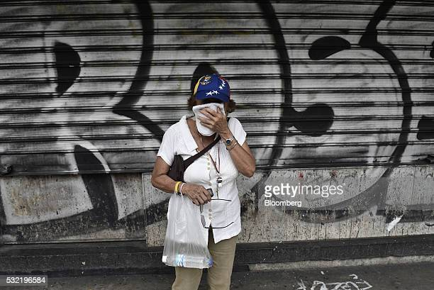 A protester wipes her face after being affected by tear gas during a demonstration in support of a referendum on the rule of President Nicolas Maduro...