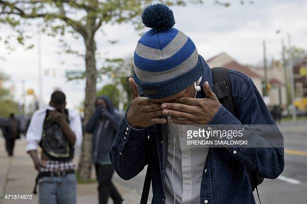 A protester wipes his eyes after pepper balls were fired by police on April 27 2015 in Baltimore Maryland Violent street clashes erupted in Baltimore...