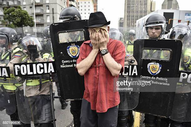 A protester wipes his face after being affected by tear gas during a demonstration in support of a referendum on the rule of President Nicolas Maduro...