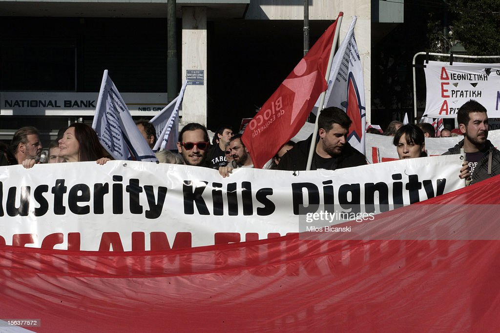 A protester with a banner says 'Austery kills dignity ' marches during an anti-austerity protest on November 14, 2012 in Athens, Greece. Unions in Spain, Portugal and Greece went on strike in what has become the first broad-based anti-austerity action to protest government plans amid a wide economic scope across Europe.