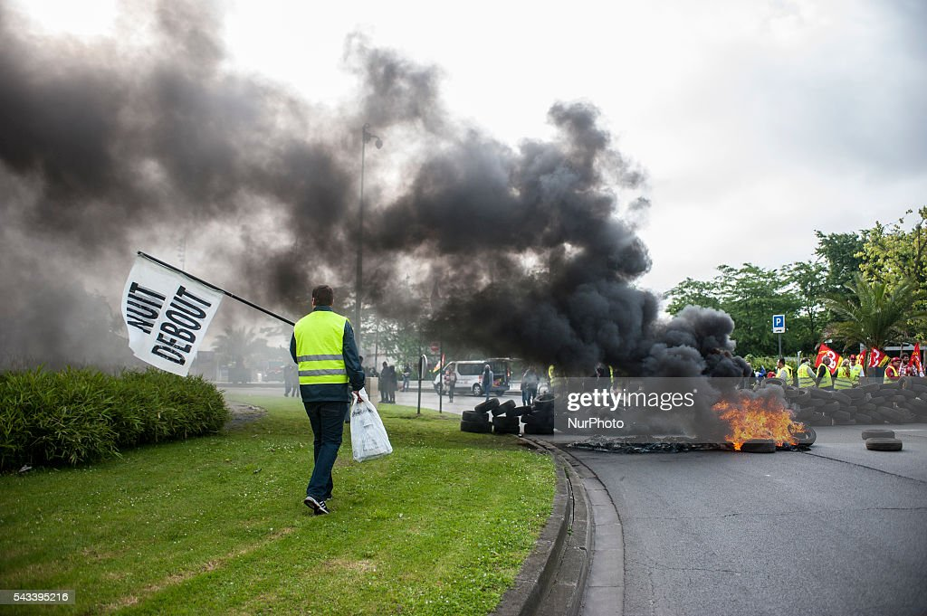 "A protester with a flag ""NIGHT STAND"" joined the blockade around the roundabout Posts blocked by trade unionists of the CGT in Lille, France on june 28, 2016. A new national day of action against the law work takes place throughout France. Economic blocking action was planned by the CGT in Lille this morning at 6:30 am."