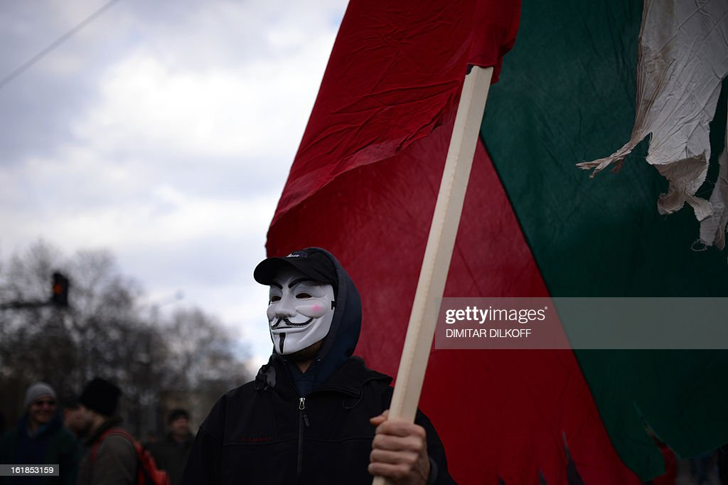 A protester with a Guy Fawkes mask waves the Bulgarian natational flag during a protest in front of the Bulgarian Parliament building in Sofia on February 17, 2013. Protesters threw rocks, firecrackers, bottles, eggs and tomatoes at the police line manning the headquarters of Czech power producer CEZ and the president's office to protest against sky-high January electricity bills in the EU's poorest country, as the government drags its feet on liberalising the energy market. AFP PHOTO / DIMITAR DILKOFF