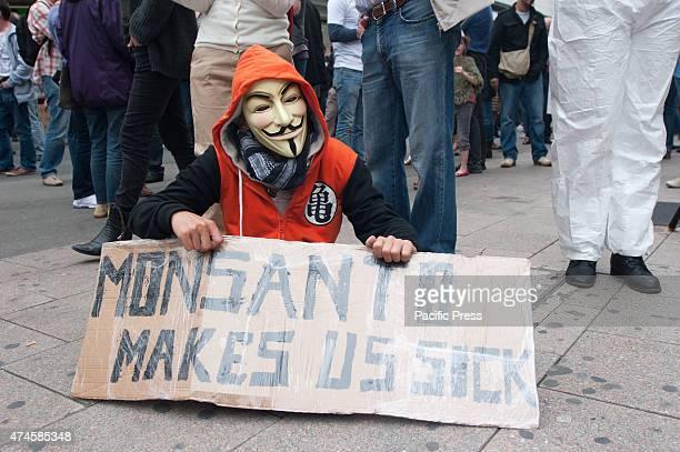 A protester with a Guy Fawkes mask with a sign that says 'Monsanto makes us sick' at the march against Monsanto in Brussels
