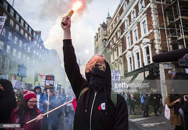 A protester with a smoke canister walks during the annual demonstration against student fees in central London on November 4 2015 Students marched...