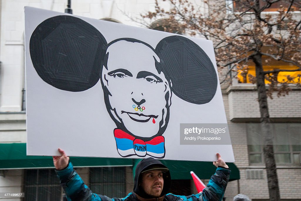 CONTENT] A protester with an anti-Putin poster depicting Putin's face with the Olympic rings, blood and Cheburashka ears during a mass demonstration against Russian troops invading Crimea, Ukraine, taken on March 2, 2014 in front of the Russian Consulate in New York City, USA.