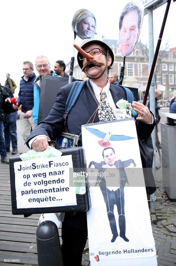 A protester with banners approach Dutch Prime Minister Mark Rutte (not seen) to stage an individual protest ahead of the elections in The Hauge, Netherlands on March 14, 2017. Elections will take place on March 15, 2017.