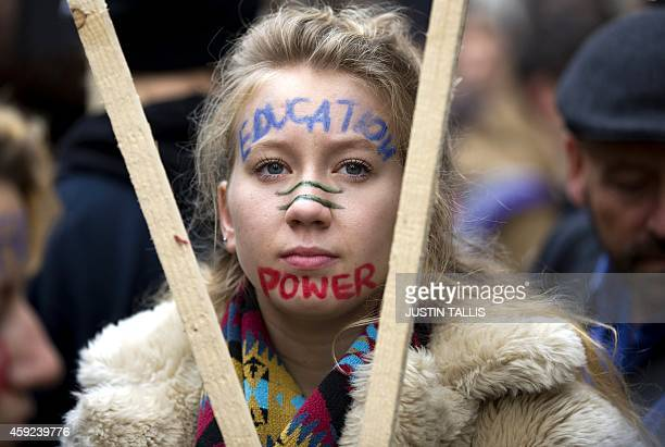 A protester with facepaint that reads 'Education Power' walks through central London during a student march against university fees on November 19...