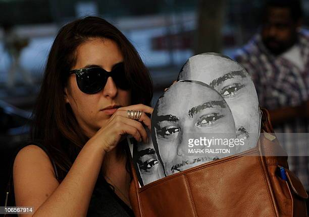 A protester with portraits of slain transit passenger Oscar Grant stands outside the Los Angeles Superior Court before the sentencing of the former...