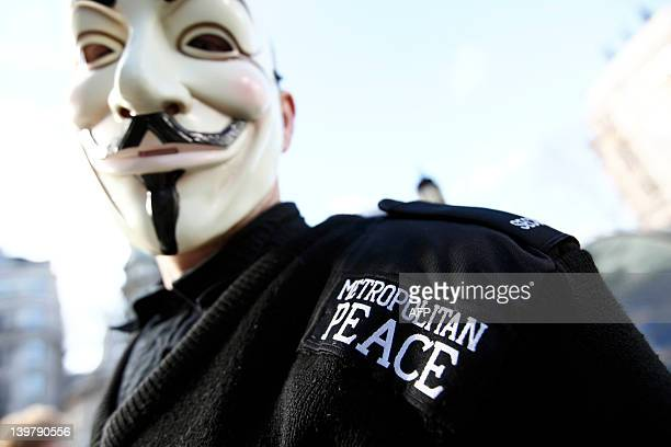 A protester with the 'Occupy London Stock Exchange' demonstration poses for a photograph wearing a Guy Fawkes 'Anonymous' mask and fake police...