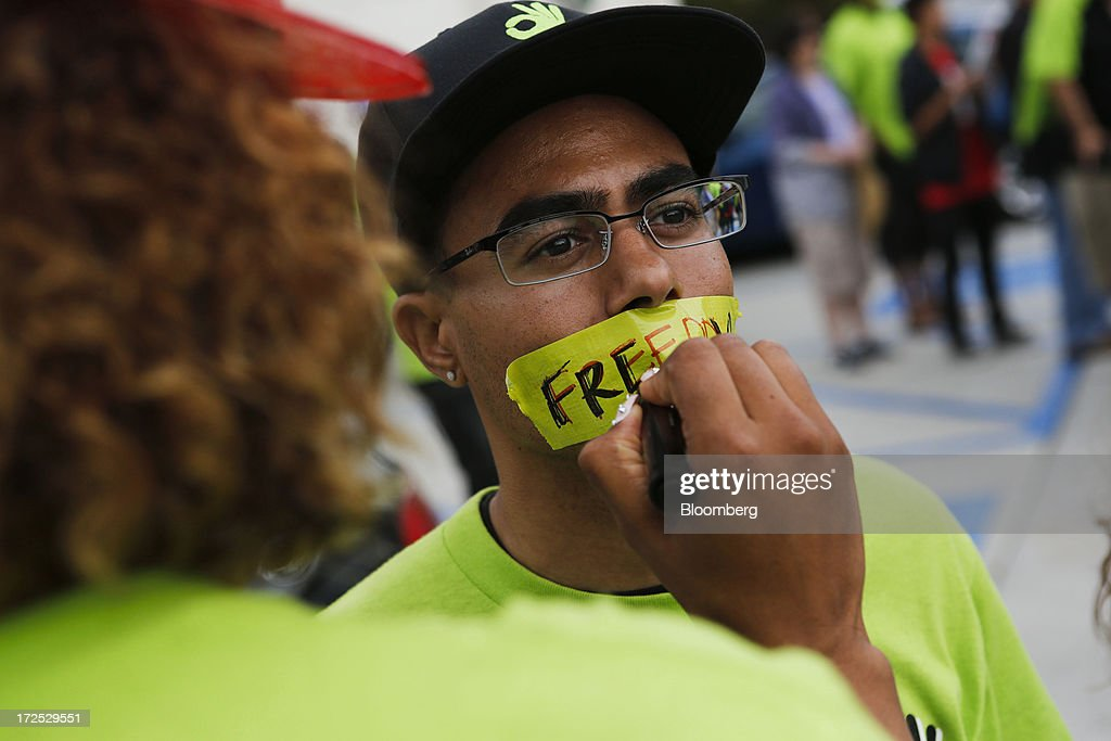A protester with the Organization United for Respect at Walmart (OUR Walmart) writes the word 'Freedom' on tape placed over the mouth of a fellow protester during a demonstration in Los Angeles, California, U.S., on Tuesday, July 2, 2013. Southern California community supporters joined Wal-Mart Stores Inc. workers to protest against alleged illegal violations of employees labor rights and freedom of speech. Photographer: Patrick T. Fallon/Bloomberg via Getty Images