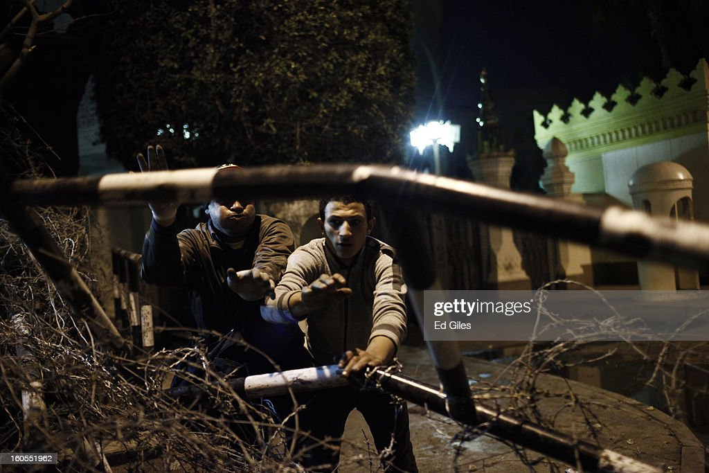 A protester works to dismantle a police barricade in front of the gates of Egypt's Presidential Palace during a demonstration following the commemoration march for a protester killed during clashes with Egyptian security forces the previous night, on February 2, 2013 in Cairo, Egypt. 23-year old protester Mohammed Hussein Korani was killed after sustaining gunshot wounds to the neck and chest during fighting with riot police outside Egypt's Presidential Palace in Cairo late on the night of February 1. Protests continued across Egypt nearly one week after the second anniversary of the Egyptian Revolution that overthrew former President Hosni Mubarak on January 25, 2011.(Photo by Ed Giles/Getty Images).