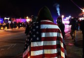 A protester wraps himself in a US flag in Ferguson Missouri on November 25 2014 during demonstrations a day after violent protests and looting...