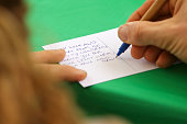 A protester writes a postcard to arrested activists during a Greenpeace protest outside the Russian Embassy on October 5 2013 in Wellington New...