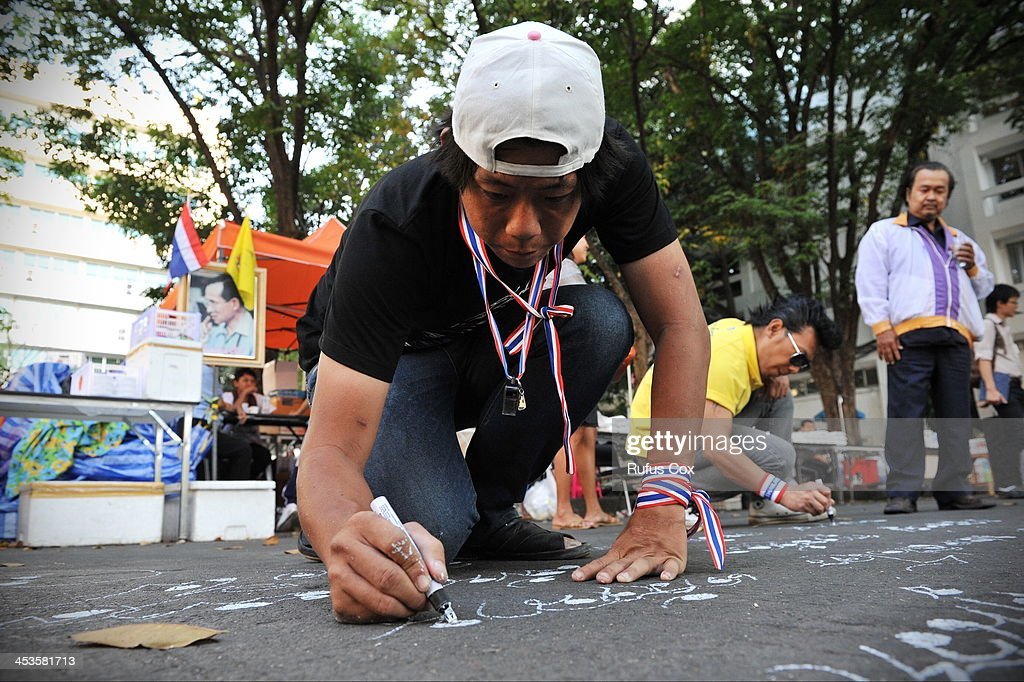 A protester writes anti-government graffiti on a road in the grounds of the Ministry of Finance, which is in its ninth day of occupation on December 4, 2013 in Bangkok, Thailand. In marking the Thai king's 86th birthday on Thursday, protesters have declared a temporary truce in their campaign to topple the government.