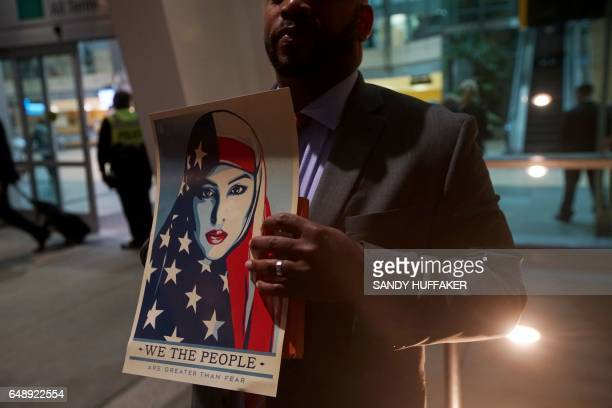A protesterholds a 'We the People' sign during a rally against the travel ban at San Diego International Airport on March 6 2017 in San Diego...