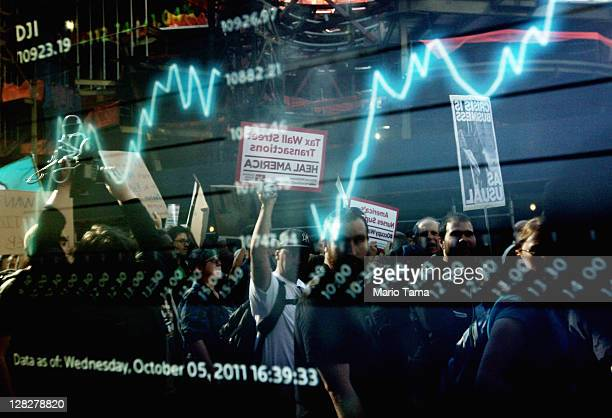 Protesters affiliated with the Occupy Wall Street movement are reflected in a stock ticket screen as they march though Lower Manhattan on October 5...