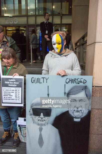 Protesters against Cardinal George Pell hold placards during Cardinal George Pell's court hearing at the Melbourne Magistrates Court in Melbourne...