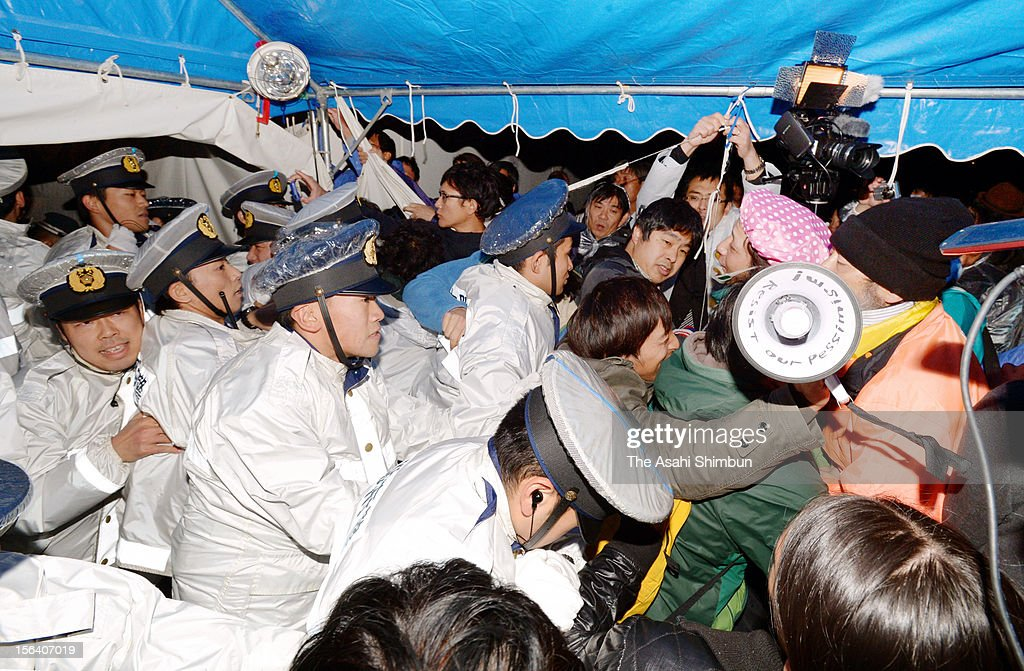 Protesters against Osaka prefecture and cities' decision to accept earthquake and tsunami debris face off with police officers at the briefing session for residents on November 14, 2012 in Osaka, Japan. Osaka will incinerate 100 tons of debris from Iwate Prefecture from November 24 to check the radiation level.