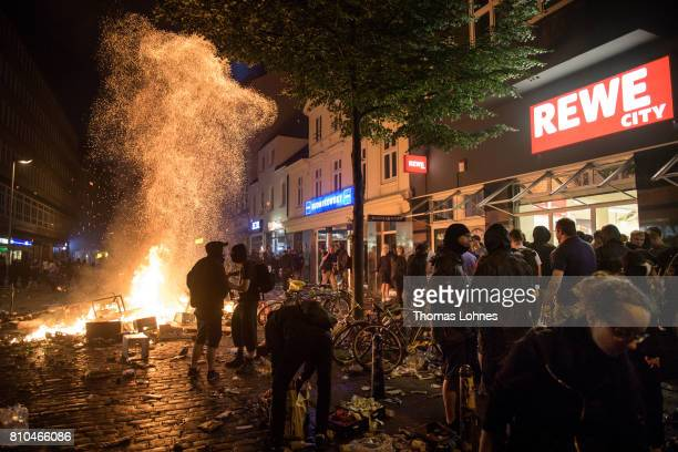 Protesters against the G20 Summit plunder a supermarket and throw the goods and installations into fires in the Schanzenviertel district on July 7...