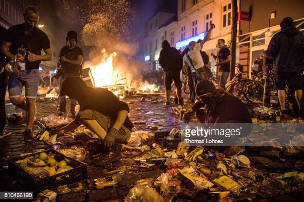 Protesters against the G20 Summit plunder a supermarket and throw the goods into fires in the Schanzenviertel district on July 7 2017 in Hamburg...