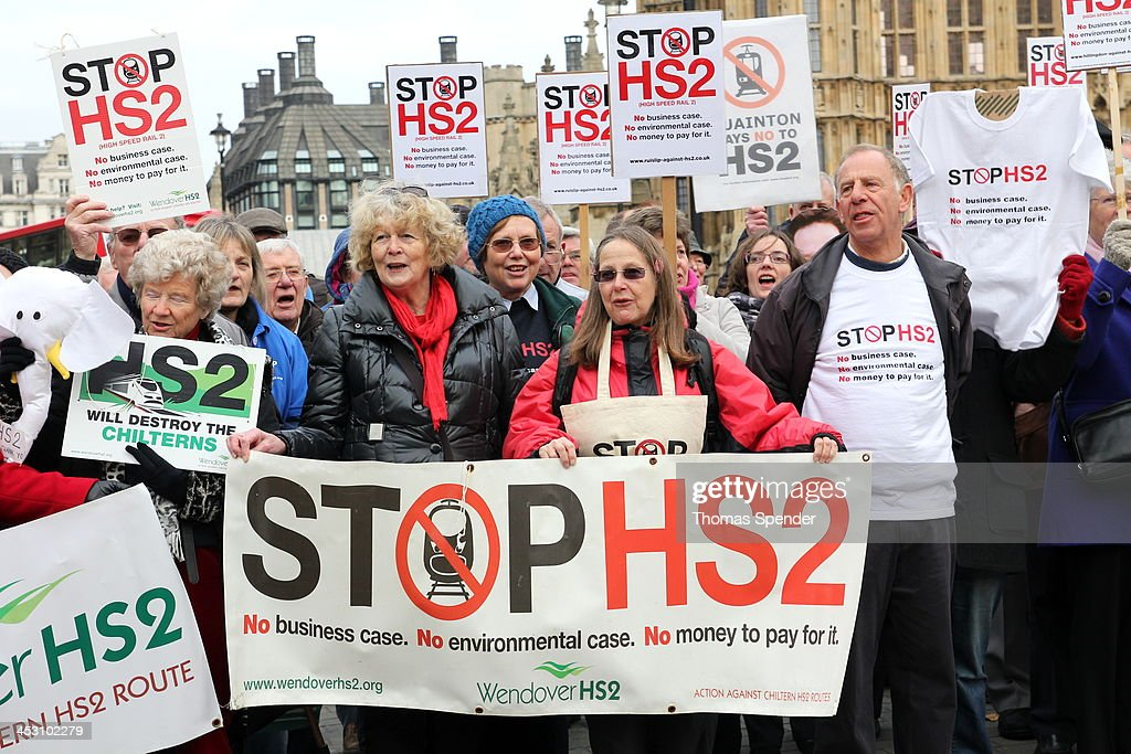 CONTENT] Protesters against the planned HS2 high speed rail link between London and Birmingham protest outside the Houses of Parliament. The government has introduced a bill for the project, which it says will increase rail capacity and boost regional business. But opponents say it's a waste of money and will suck more economic activity into London.