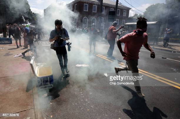 Protesters and journalists pull back after tear gas was used on the outskirts of Emancipation Park during the Unite the Right rally August 12 2017 in...
