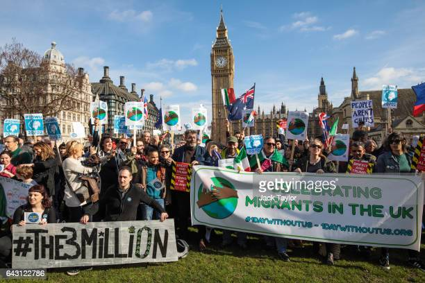 Protesters and migrant workers hold banners and flags as they demonstrate outside Parliament on February 20 2017 in London England A day of action in...