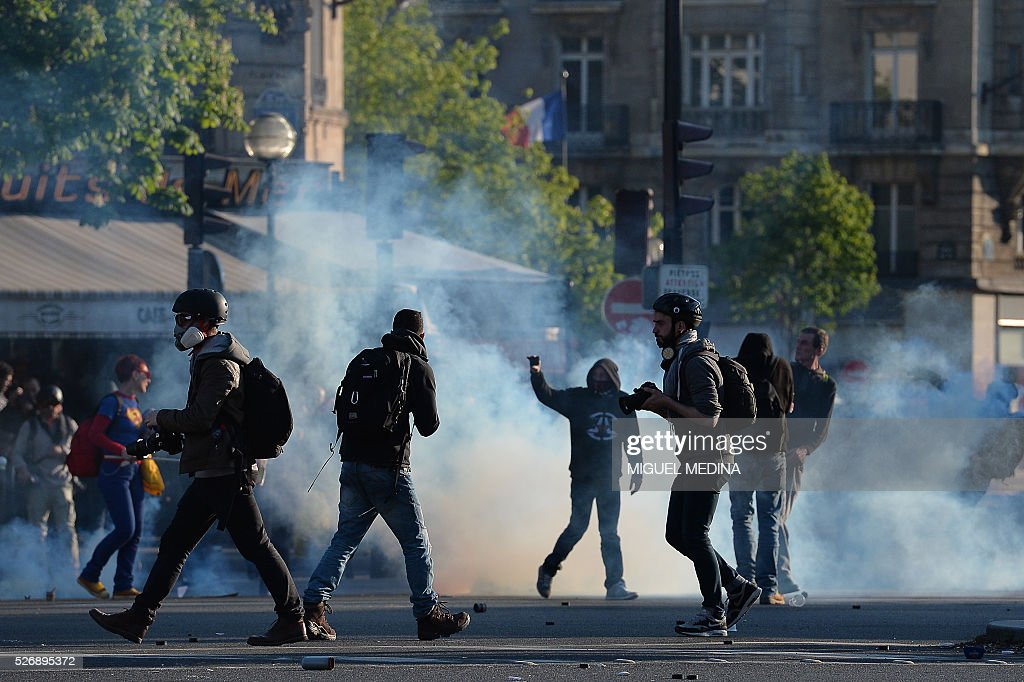 Protesters and photographers stand on the Place de la Republique during clashes with police at a traditional May Day demonstration on May 1, 2016, in Paris.