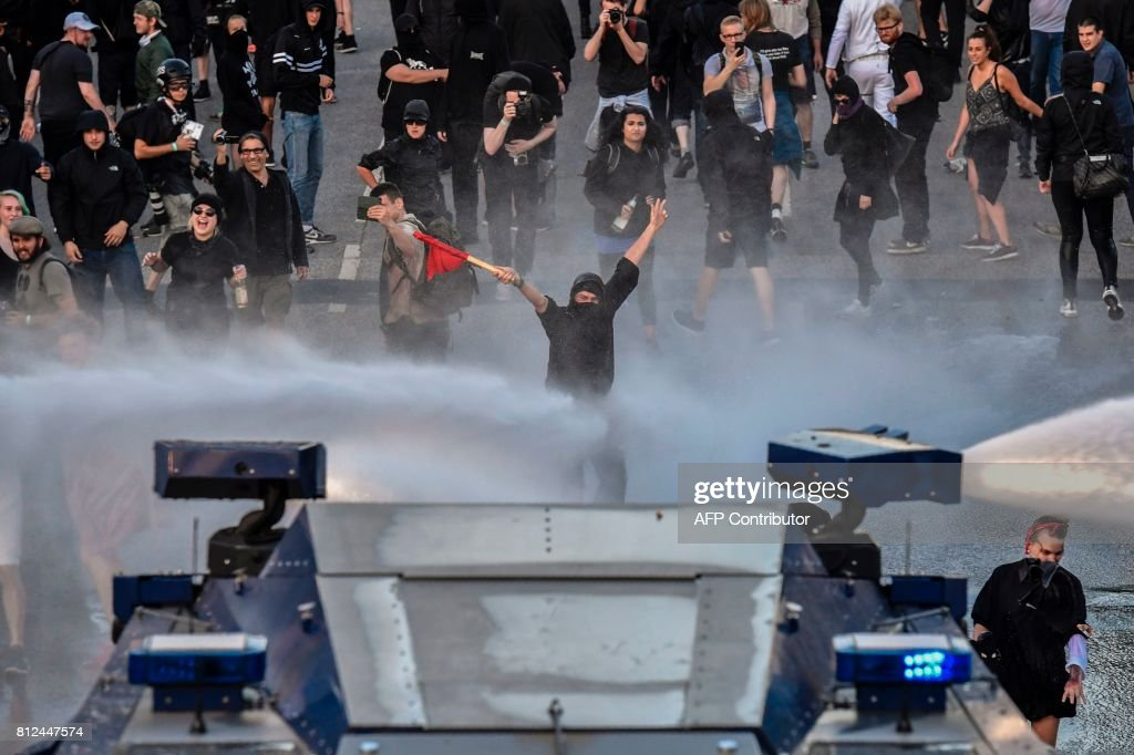 TOPSHOT - Protesters are doused with water during the 'Welcome to Hell' rally against the G20 summit in Hamburg, northern Germany on July 6, 2017. Leaders of the world's top economies will gather from July 7 to 8, 2017 in Germany for likely the stormiest G20 summit in years, with disagreements ranging from wars to climate change and global trade. / AFP PHOTO / John MACDOUGALL
