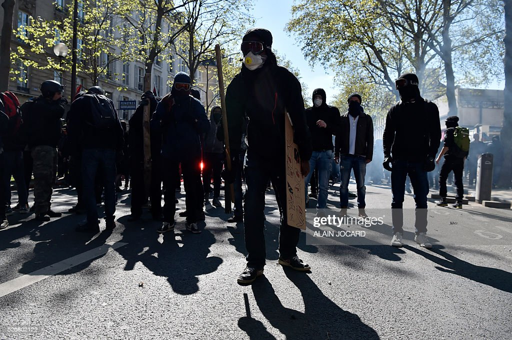 Protesters are pictured during a clash with French anti riot police during the traditional May Day demonstration in Paris on May 1, 2016.