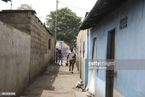 Protesters are seen running down a narrow street where opposition supporters have erected makeshift barricades and block roads in Lome on October 18...