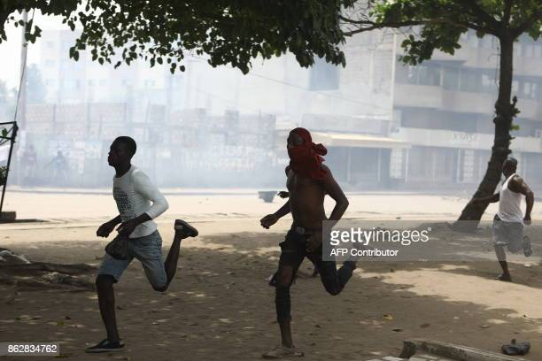 Protesters are seen running down a street where opposition supporters have erected makeshift barricades and block roads in Lome on October 18 2017...