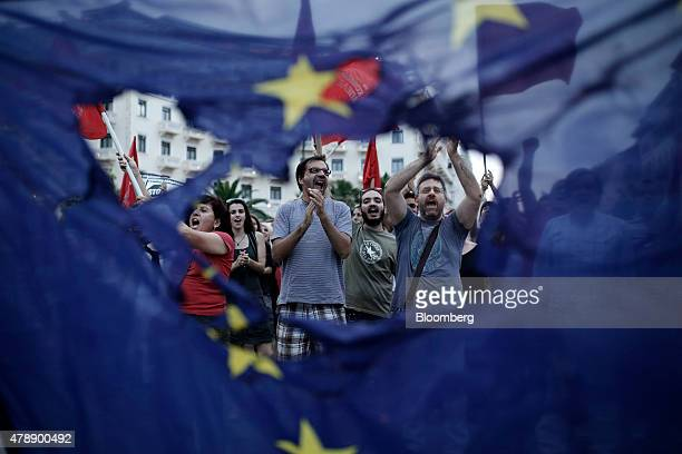 Protesters are seen through a burned European Union flag during an antiausterity demonstration in Thessaloniki Greece on Sunday June 28 2015 Greece...