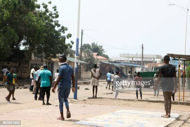 Protesters are seen walking in the streets as opposition supporters erect makeshift barricades and block roads in Lome on October 18 2017 Protesters...