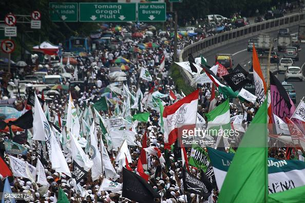 Protesters are waving their flag during the protestThousands of Muslims from various organizations that are members of the Islamic People's Front...