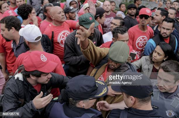Protesters argue with Brazilian security forces during a demonstration organized by Homeless Workers Movement as they prepare to march to the...