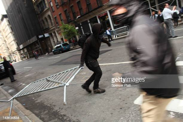 Protesters associated with the Occupy Wall Street movement pull down police barricades while marching through traffic in lower Manhattan on May 1...