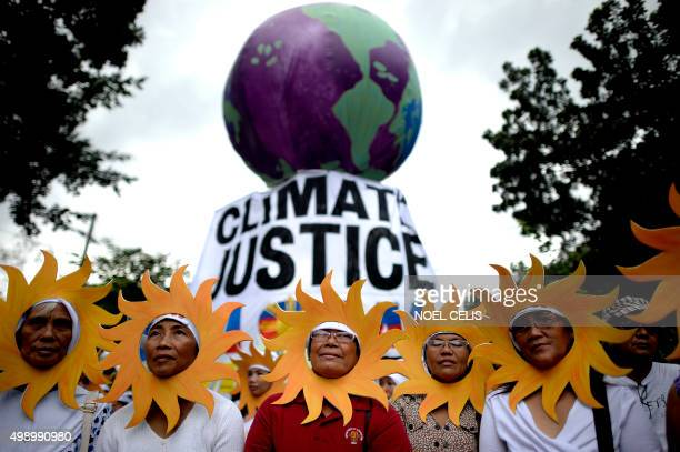 Protesters attend a climate change march on a highway in Manila on November 28 2015 Thousands turned out for climate change marches in Manila and...